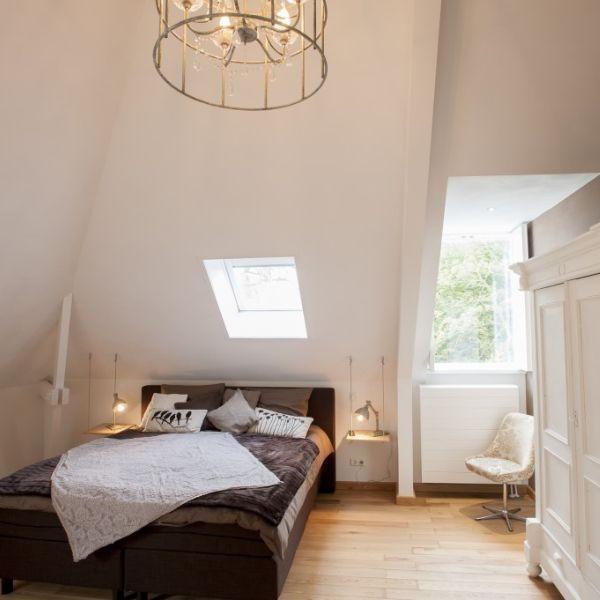 Villa Heidetuin, kamer, witte interieur, zwart grijze bed en antieke lamp