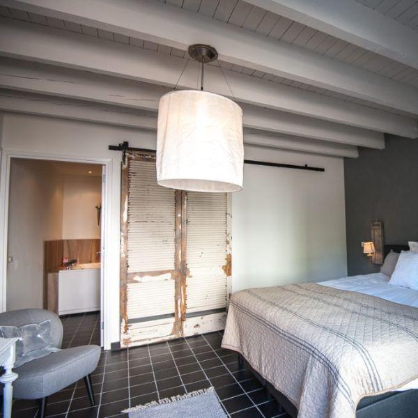Villa Heidetuin, kamer, witte muur, grijze muur, grijze stoel, rustieke deur en lamp