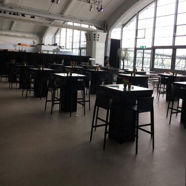 Cruise Terminal Rotterdam, ruimte, zwarte hoge stoelen, witte plafond en donker grijze vloer.